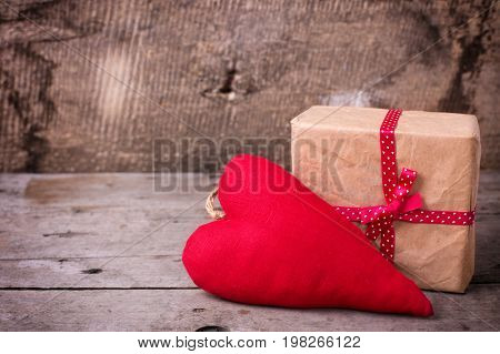 Festive gift box and decorative red heart on vintage wooden background. Selective focus. Place for text.