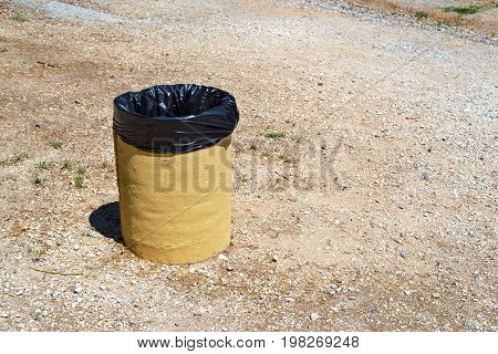 one old bin for garbage against the background of the empty earth or soil
