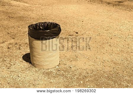 one old bin for garbage against the background of the empty earth or soil with effect sepia