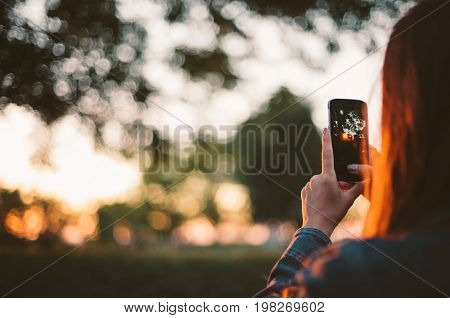 Girl taking photo of sunset on smartphone