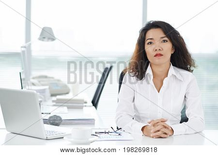 Portrait of unsmiling VIetnamese business lady sitting at her table