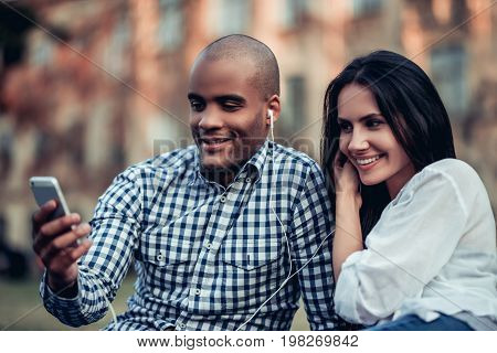 Beautiful interracial couple is sharing earphones listening music from smart phone and smiling.