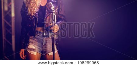 Midsection of young singer performing at concert in nightclub