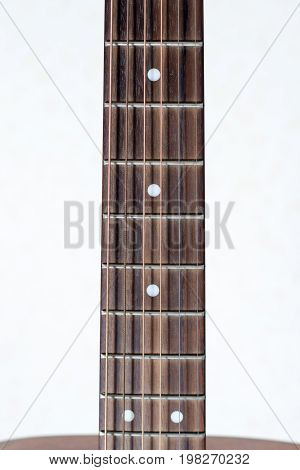 Close-up neck of guitar on a white background