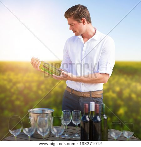 Young man holding wine bottle by glasses on barrel against scenic view of beautiful mustard field