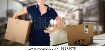 Happy delivery woman holding cardboard box  against many stack of cardboard boxes