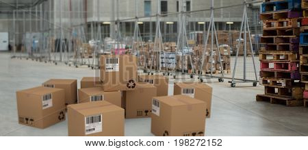 Group of composite cardboard boxes against image of a warehouse