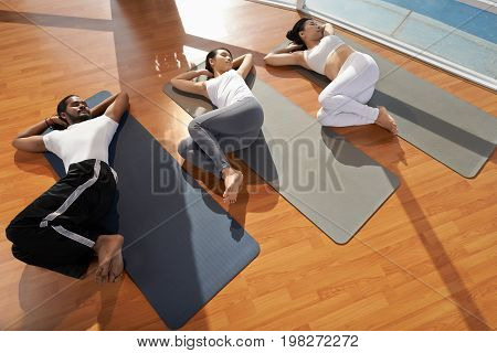 People performing supine spinal twist, view from above