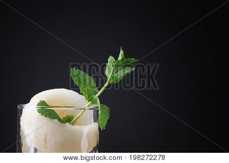 A transparent glass full of alcohol cocktail with a piece of carved melon on a saturated black background. Sour, cold and alcoholic mojito with melon and mint. Copy space.