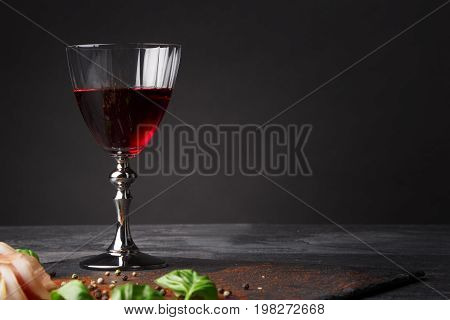 A shiny glass full of sweet wine, piquant meat and spicy basil on a saturated black background. The composition of yummy snacks and dark red beverage on the table. Delicious prosciutto and wine. Copy space.