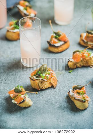 Crostini with smoked salmon, pesto sauce, watercress and capers and pink grapefruit cocktails over grey background, selective focus, copy space. Party, catering or fingerfood concept