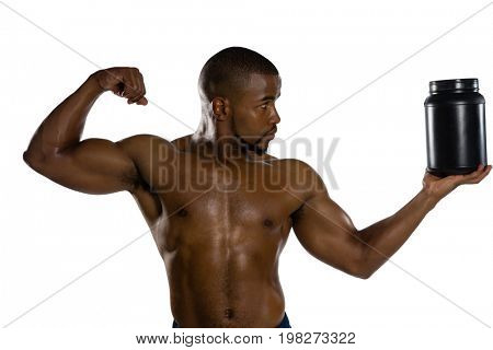 Shirtless male athlete flexing muscles while holding supplement jar against white background