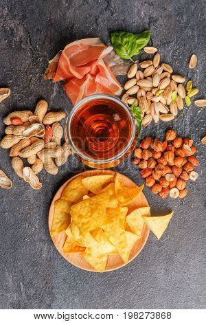A top view of light beer and spicy, salty snacks on a gray background. A heap of chips, nuts, pistachios and cut prosciutto on the desk. Fresh green spinach leaves and a lot of snacks for beer.