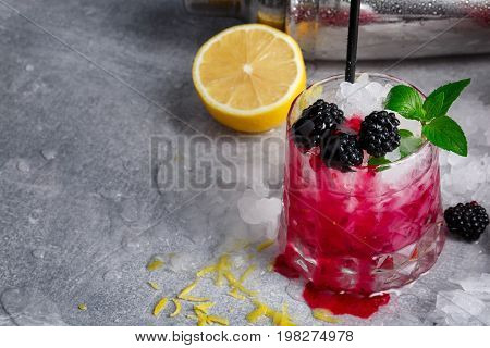 Close-up of a glass full of tasty, cold, beverage with blackberries, mint, lemon, and cubes of ice on a light gray background. The cocktail with black straw and berries. Juicy lemon near the drink. Copy space.