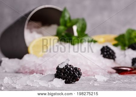 A juicy, ripe, and sweet blackberry on a blurred background. A metal bucket with crushed ice, a slice of sour lemon and fresh mint as a background. Refreshing summer ingredients.