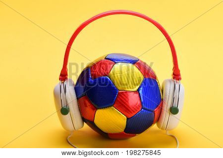 Music and sports equipment concept. Headphones in white and red color with colorful soccer ball. Modern earphones and football isolated on light orange background. Headset for music placed on ball