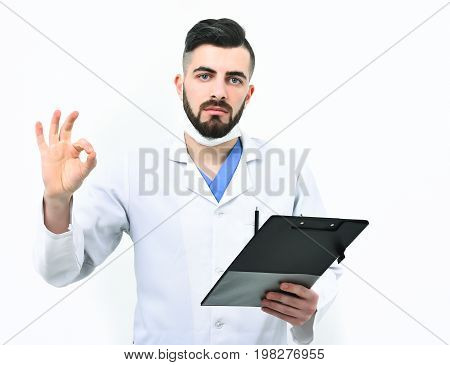 Guy in surgical mask isolated on white background. Treatment and ambulance service concept. Man with serious face in white coat. Doctor with beard holds clip folder for prescriptions and shows ok sign
