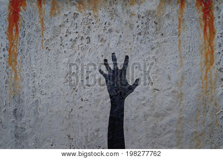 Left corpse hand silhouette in shadow on concrete wall and blood background. Zombie and halloween theme illustration.