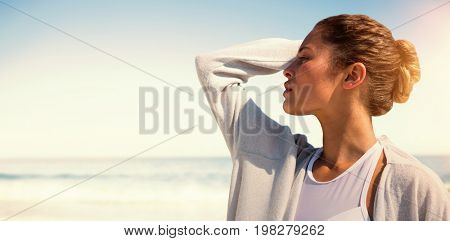 Profile view of a woman posing with hand in the hair  against scenic view of beach
