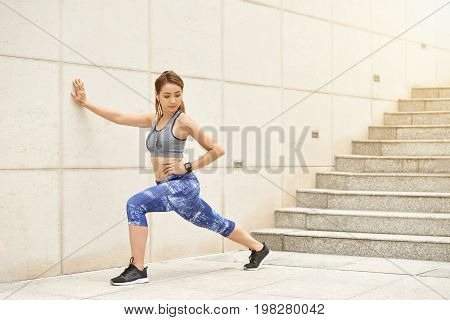 Lovely Vietnamese sportswoman doing stretching exercise after running