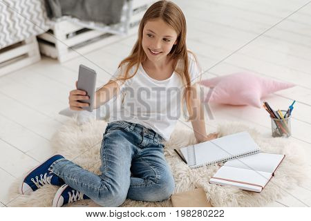 Updating social media. Positive minded young lady sitting on the floor and posing while taking selfies on her phone at home.