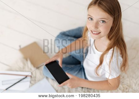 Technological generation. Top view on a grey eyed girl in casual smiling for the camera while using her smartphone and doing her home assignment on the floor.