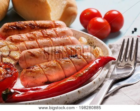 Close up view of chicken homemade sausages with buns bread. Grilled sausages and grilled vegetables in craft trendy plate. Home hotdogs.