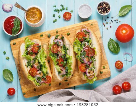 Top view of homemade hotdogs with chicken sausages, fresh vegetables, ketchup and mustard sauce on blue wooden background. Hot-dogs with tomatoes, onion, basil, letucce and spices.