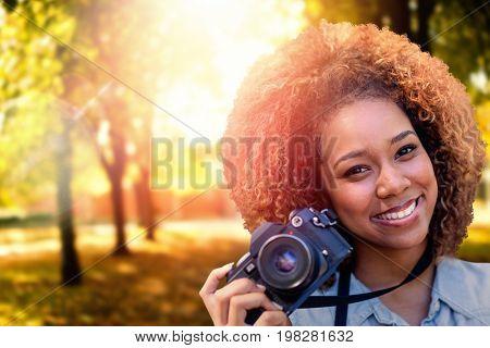 Headshot of smiling girl against defocused image of trees growing at park