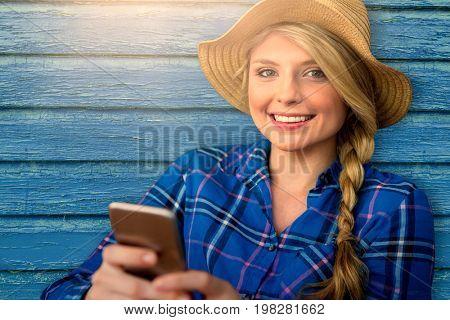 Smiling girl holding smartphone against full frame shot of blue wall