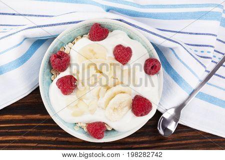 Fresh healthy breakfast. Oatmeal with yogurt and fresh raspberries and banana. Healthy breakfast oatmeal eating.