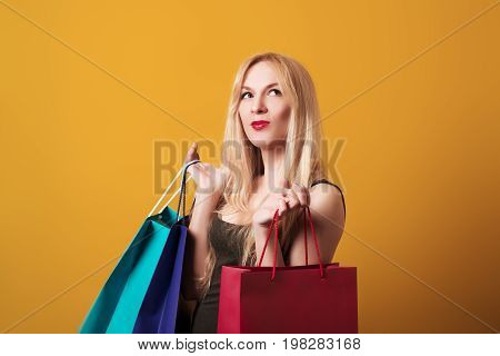 Young blondy girl holding shopping bags isolated over the yellow background.