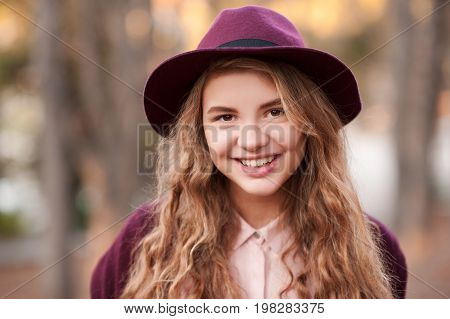 Smiling blonde teen girl 14-16 year old wearing purple hat and jacket outdoors. Looking at camera. Autumn season.