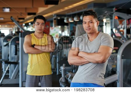 Asian smiling fitness instructors standing with their arms crossed and looking at camera