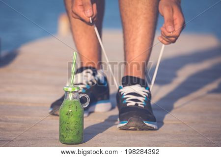 Green smoothie fitness man lacing running shoes. Athlete runner with green vegetable detox juice getting ready for morning run tying running shoe laces on wooden dock. Fitness and healthy lifestyle concept.