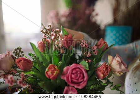 woman florist making bouquet of flowers indoor. Female florist preparing bouquet with roses tulip in flower shop. Close up