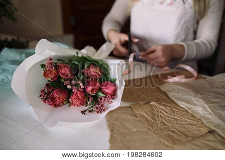 woman florist making bouquet of flowers indoor. Female florist preparing bouquet with tulip in flower shop. Close up