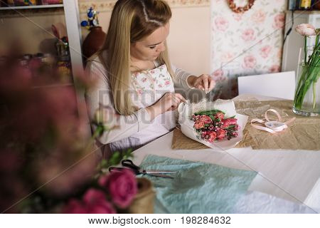 woman florist making bouquet of flowers indoor. Female florist preparing bouquet with tulip in flower shop.