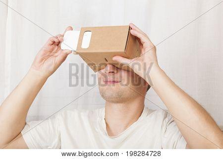Handsome adult man using cardboard virtual reality gloves cardboard. Future of work virtual reality.