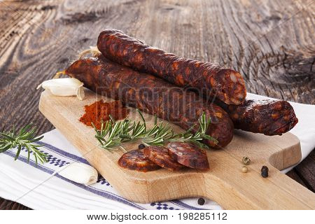 Traditional sausage with pepper garlic thyme and rosemary on wooden chopping board. Delicious homemade traditional sausages.
