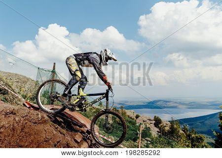 Magnitogorsk Russia - July 21 2017: rider mountain biking background of clouds and lake during National championship downhill