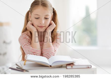 Education is the key to success. Diligent little student looking at her book while reading new information and preparing a home assignment for tomorrow.