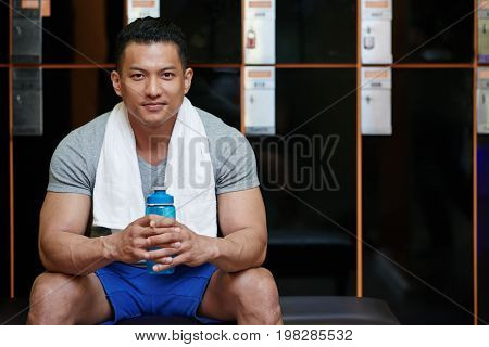 Portrait of smiling Malaysian sportsman sitting in locker room with bottle of water