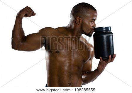 Shirtless sports man kissing supplement jar while flexing muscles
