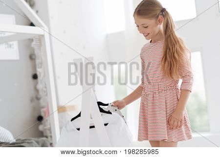 What should I wear today. Beautiful young lady standing at her closet and holding and enjoying the process of choosing her attire at home.