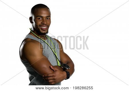 Portrait of smiling male instructor with arms crossed standing against white background
