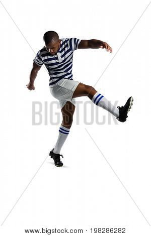Full length of male rugby player kicking against white background