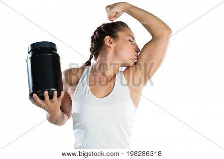 Female athlete holding supplement jar while kissing biceps against white background