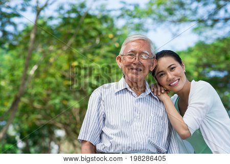 Portrait of happy senior man and his adult daughter leaning on his shoulder