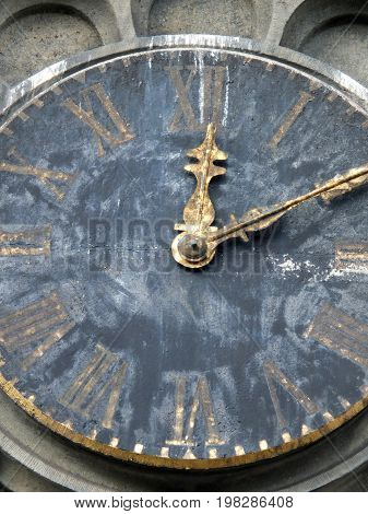 old weathered church tower clock with roman numerals and gold hands stopped at then past twelve with fading paint